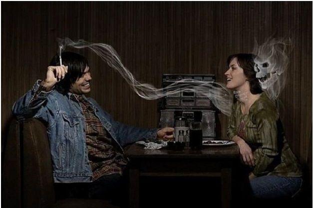 Парень курит сигарету напротив девушки